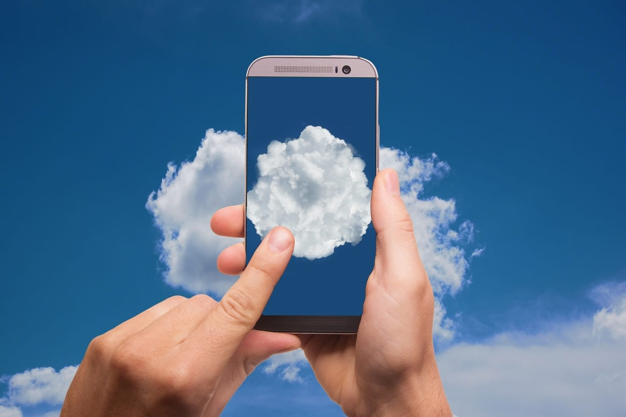 cell-phone-against-cloudy-sky-background